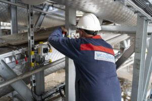 Servicemonteur werkt aan het installeren van een schroefwarmtewisselaar